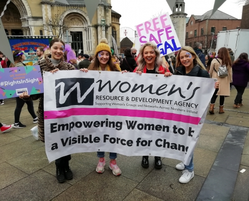 Young women holding WRDA's banner at International Women's Day 2020.