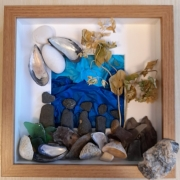 Box frame using stones and shells to create a representation of a family.