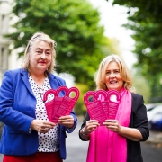 Katherine Robertson and Paula Murray with waterproof cards that hang in the shower to give instructions on the best procedure for breast self-examination.